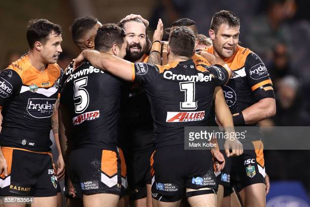 Aaron Woods of the Tigers celebrates with his team after scoring a try during the round 25 NRL match between the Wests Tigers and the North...