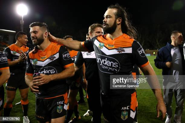 Aaron Woods of the Tigers embraces team mate James Tedesco of the Tigers after winning the round 26 NRL match between the Wests Tigers and the New...