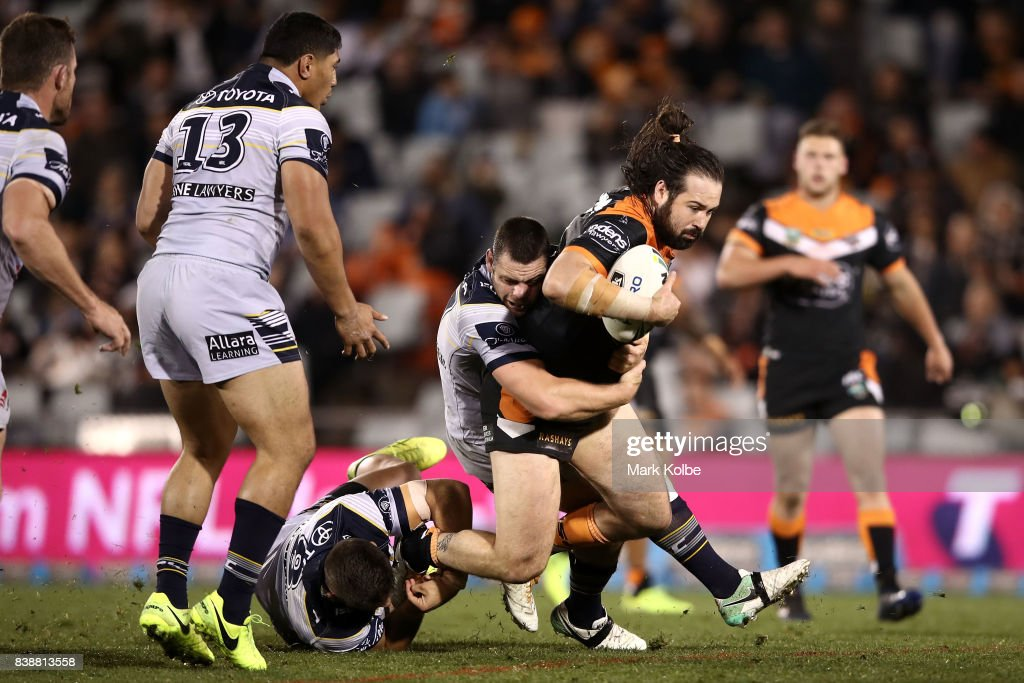 Aaron Woods of the Tigers is tackled by during the round 25 NRL match between the Wests Tigers and the North Queensland Cowboys at Campbelltown Sports Stadium on August 25, 2017 in Sydney, Australia.