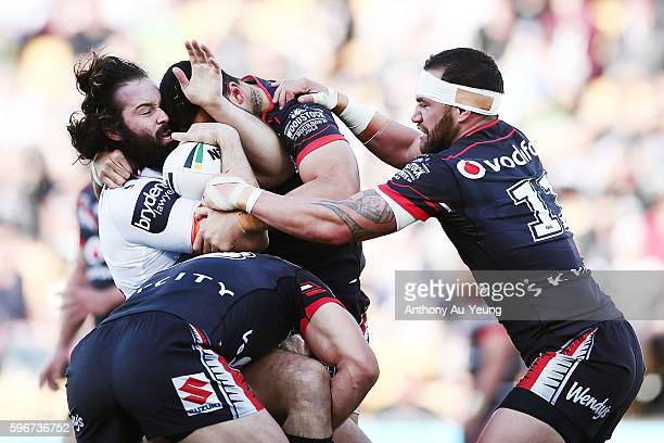 Aaron Woods of the Tigers is tackled by Simon Mannering and Bodene Thompson of the Warriors during the round 25 NRL match between the New Zealand...