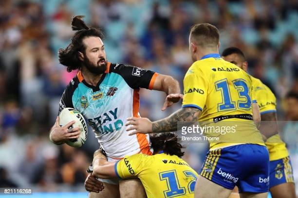Aaron Woods of the Tigers is tackled by the Eels defence during the round 20 NRL match between the Wests Tigers and the Parramatta Eels at ANZ...