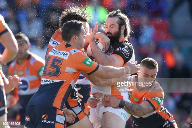 Aaron Woods of the Tigers is tackled during the round 17 NRL match between the Newcastle Knights and the Wests TIgers at McDonald Jones Stadium on...