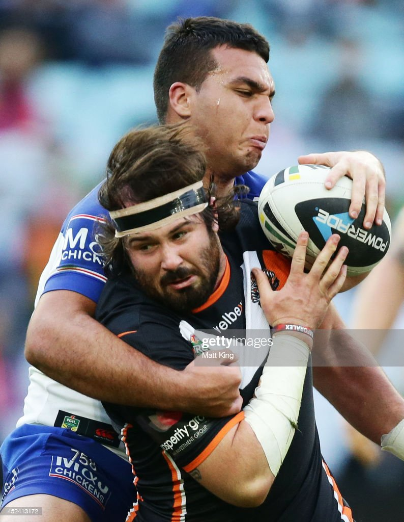 Aaron Woods of the Tigers is tackled during the round 19 NRL match between the Wests Tigers and the Canterbury Bulldogs at ANZ Stadium on July 20, 2014 in Sydney, Australia.