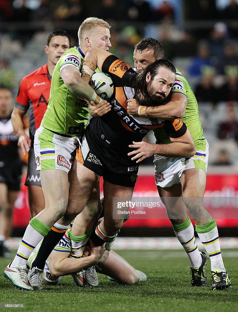 Aaron Woods of the Tigers is tackled during the round 22 NRL match between the Canberra Raiders and the Wests Tigers at GIO Stadium on August 10, 2015 in Canberra, Australia.