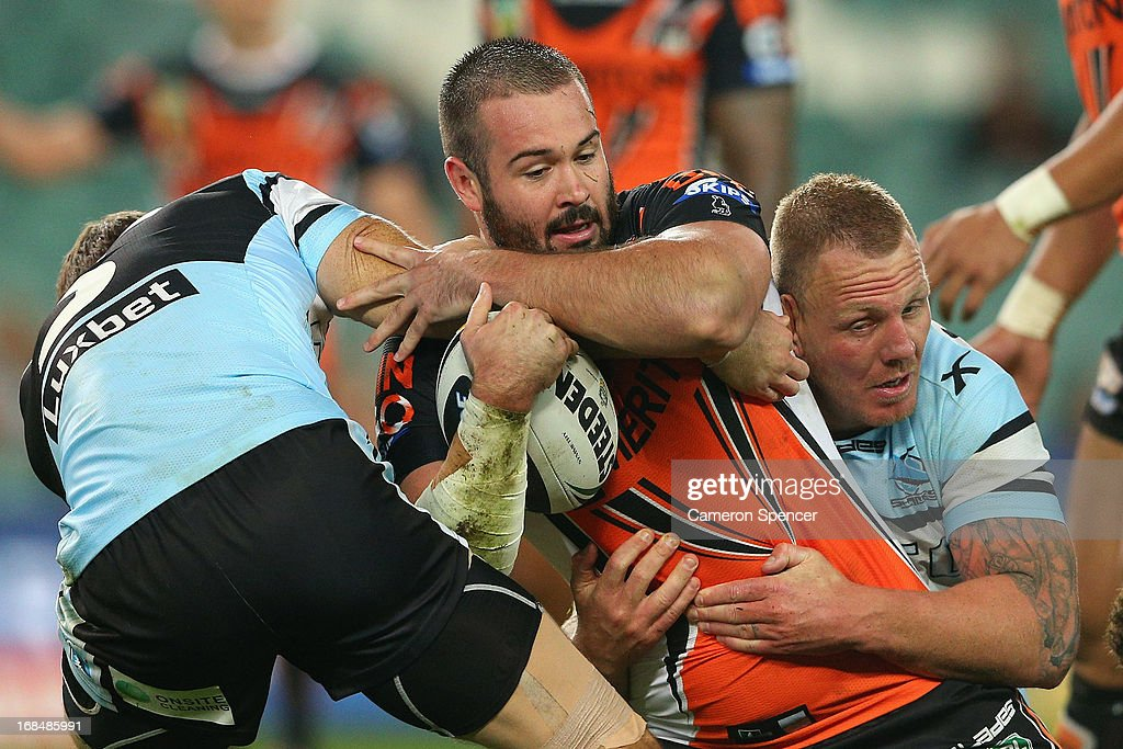 Aaron Woods of the Tigers is tackled during the round nine NRL match between the Wests Tigers and the Cronulla Sharks at Allianz Stadium on May 10, 2013 in Sydney, Australia.