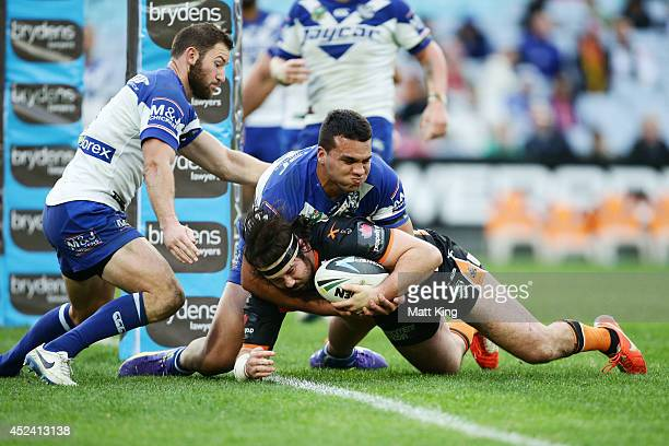 Aaron Woods of the Tigers scores a try during the round 19 NRL match between the Wests Tigers and the Canterbury Bulldogs at ANZ Stadium on July 20...