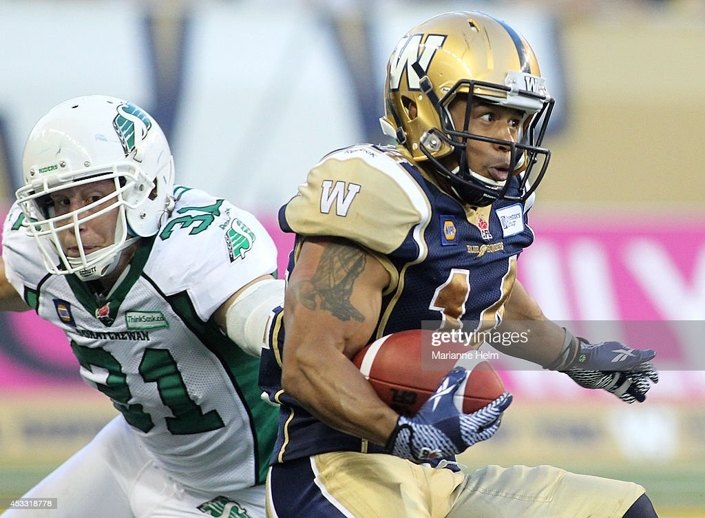 Aaron Woods #14 of the Winnipeg Blue Bombers gets by Samuel Hurl #31 of the Saskatchewan Roughriders in first half action in a CFL game at Investors Group Field on August 7, 2014 in Winnipeg, Manitoba, Canada.