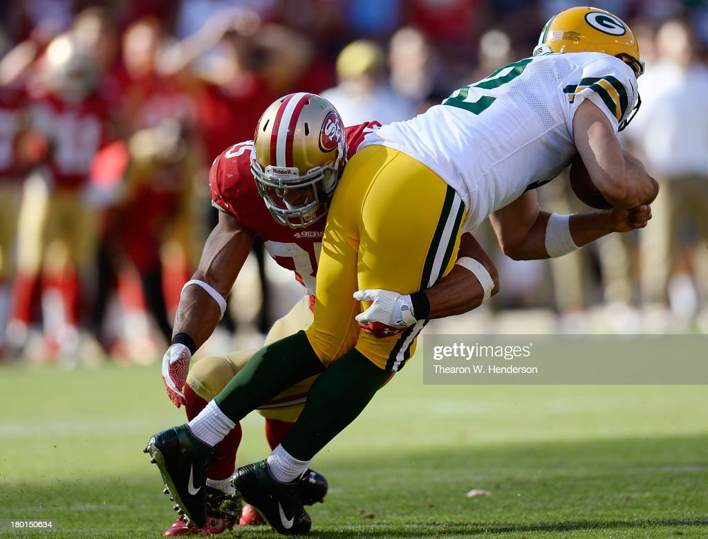 Aarron Rogers #12 of the Green Bay Packers scrambles with the ball for seven yards and gets tackled by Eric Reid #35 of the San Francisco 49ers during the fourth quarter at Candlestick Park on September 8, 2013 in San Francisco, California.
