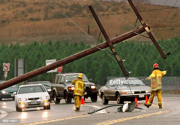 AAStormPowerPole092597MB–––Firefighters from the Orange County Fire Authority diverted traffic away from a downed power pole––still live–– carrying...