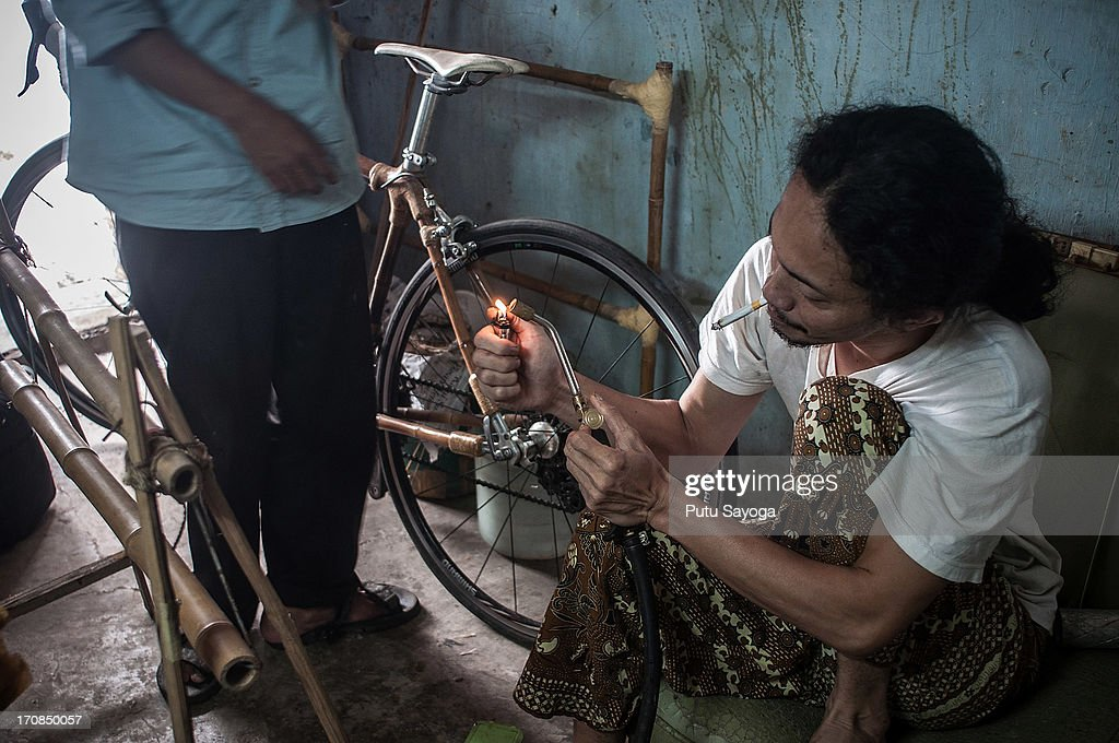 Abah lights a flame on a tool used in the construction of a bamboo bike frame at Haur Bike workshop on June 19, 2013 in Bandung, Java, Indonesia. Two friends, Abah and Gun Gun Gunawan converted Abah's small guest room into a workshop in the Neglasari district in order to make bamboo bikes with sustainable phyllostachys aurea bamboo using DIY tools. They have named their product 'Haur Bike'.