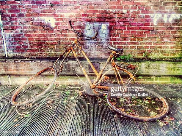 Abandoned And Damaged Bicycle Against Brick Wall