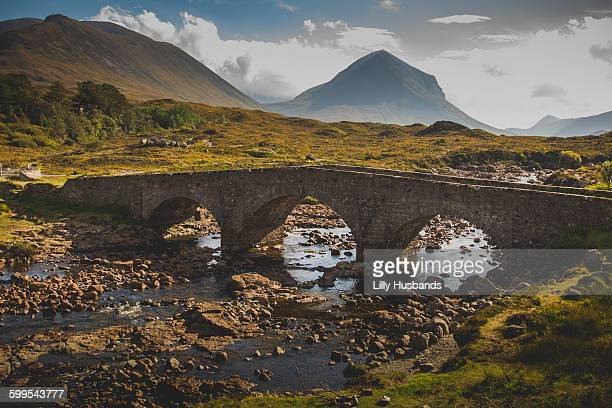 Abandoned arch bridge over stream against mountains