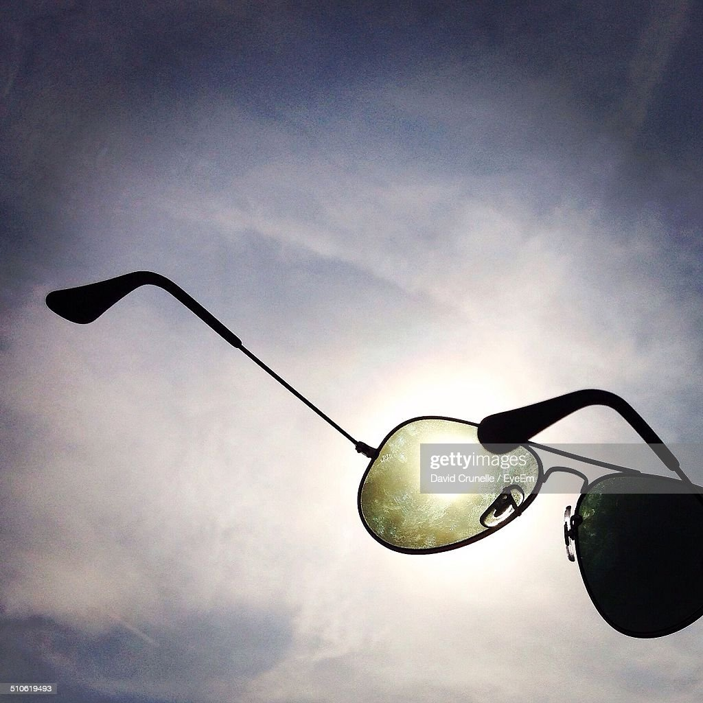Abandoned aviator glasses against cloudy sky