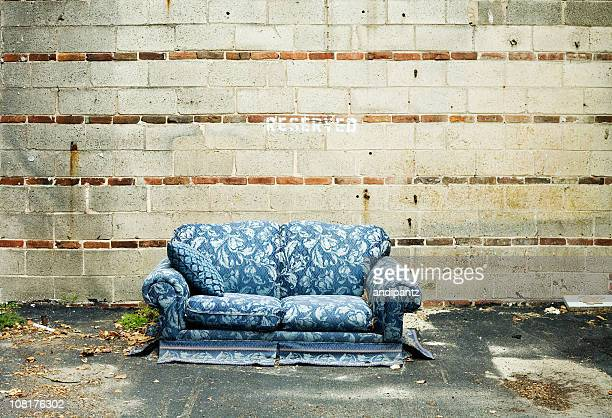 Verlassenen Blue Couch sitzen gegen Zement-Wand im Freien