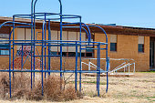 Closeup of an abandoned blue monkey bars in tall grass. School building in background.