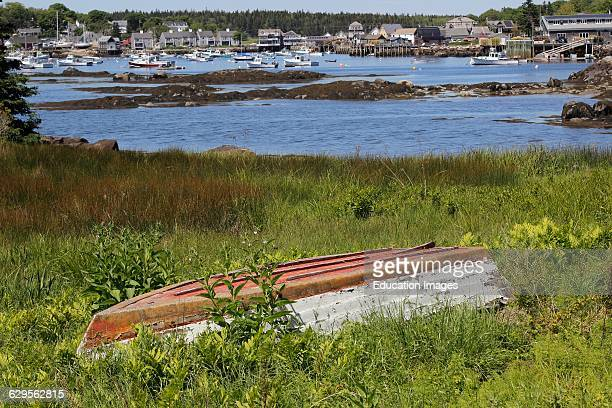 abandoned boat in grass at harbor Vinalhaven Island Maine New England USA