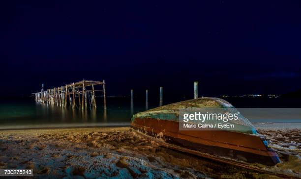 Abandoned Boats Moored In Lake Against Sky At Night