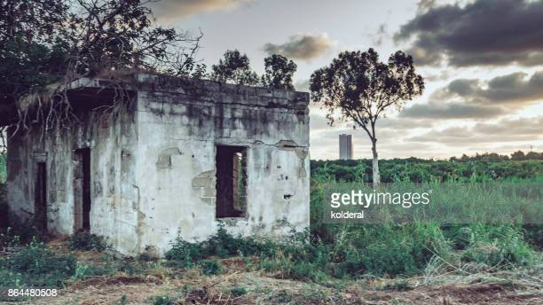 Abandoned building in the field view of distant modern office towers during sunset