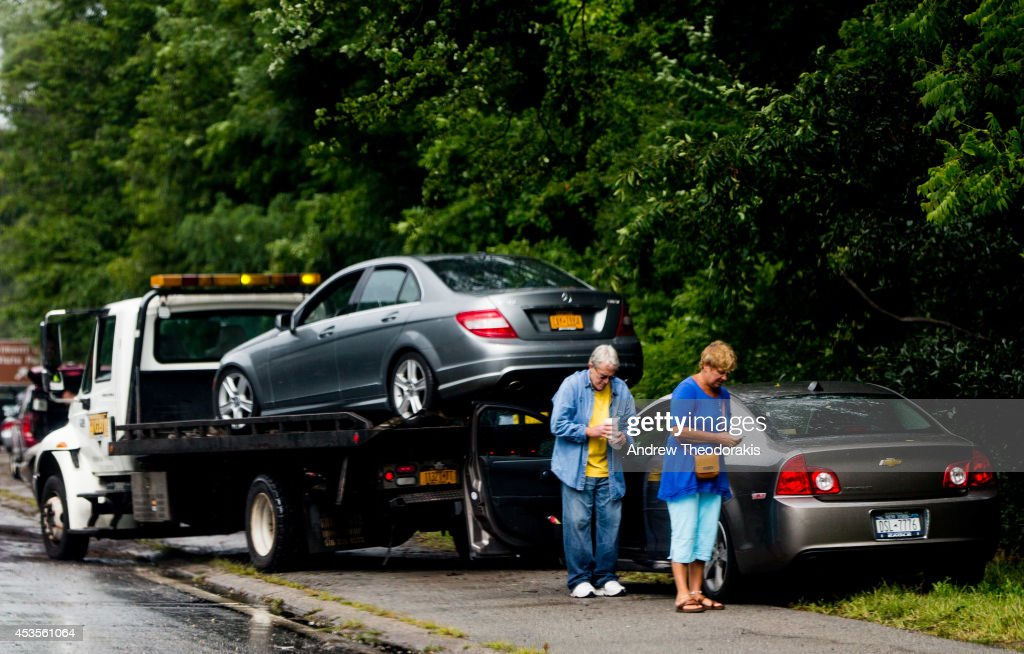 Abandoned cars are towed from the Southern State Parkway following heavy rains and flash flooding August 13, 2014 in Babylon, New York. The south shore of Long Island along with the tri-state region saw record setting rain that caused roads to flood entrapping some motorists.