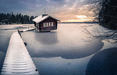 Abandoned cottage with sunset at winter evening in Finland