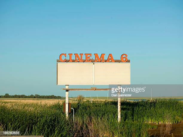 Abandoned drive-in movie sign in field