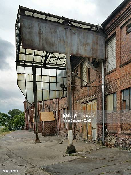 Abandoned Factory Building By Street Against Cloudy Sky