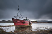 An old wooden hulled fishing boat, now abandonded and being left to rot
