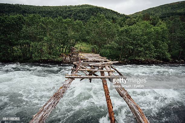 Abandoned Footbridge Over River Against Mountain In Forest