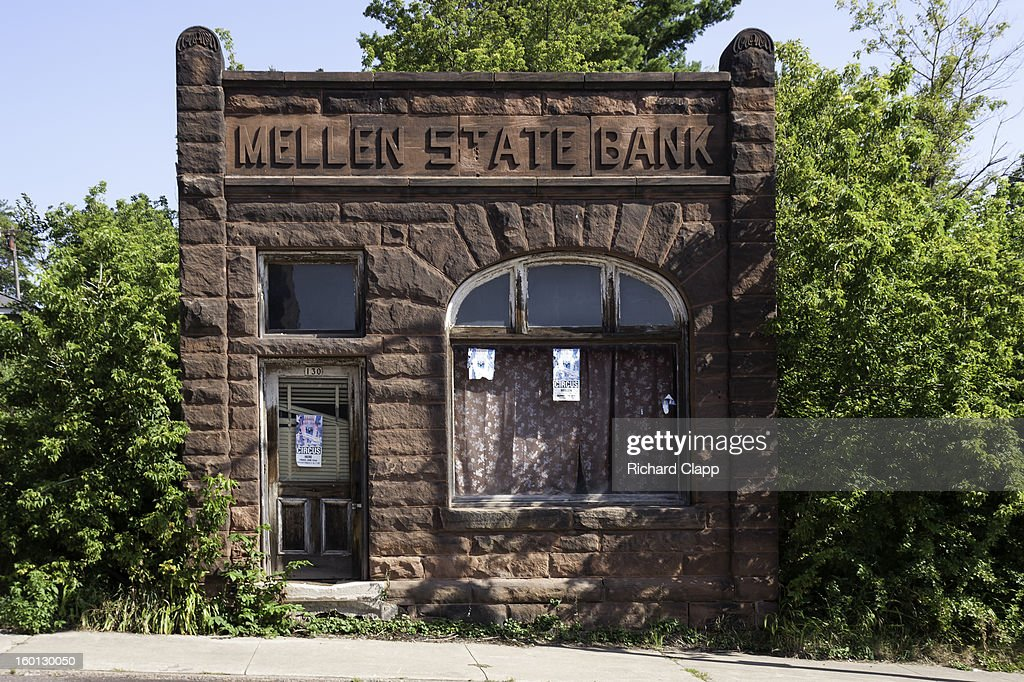 CONTENT] Abandoned historic brownstone building, 'Mellen State Bank', with encroaching vegetation on the main street of this small north western Wisconsin town.