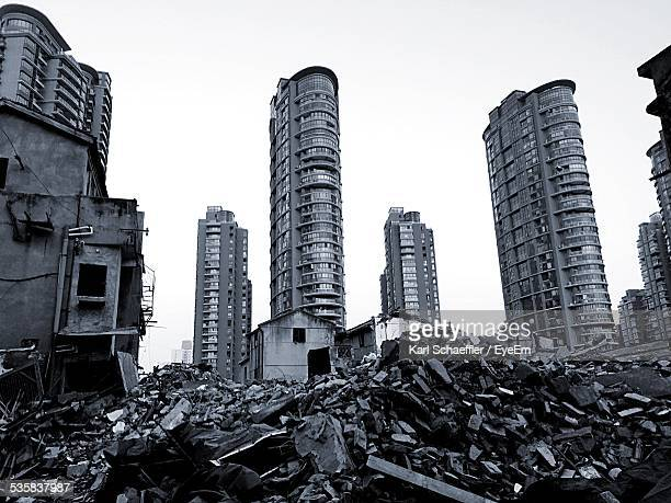 Abandoned Houses And Modern Buildings Against Clear Sky