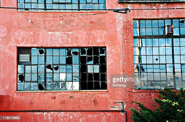 Abandoned industrial red brick building with broken windows