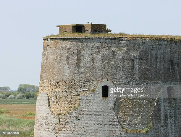 Abandoned Martello Tower On Field Against Clear Sky