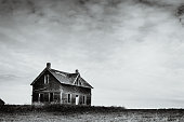 An old farm house sits abandoned on the prairies.