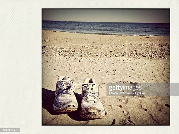 Abandoned Pair Of Shoes On Beach Against Clear Sky
