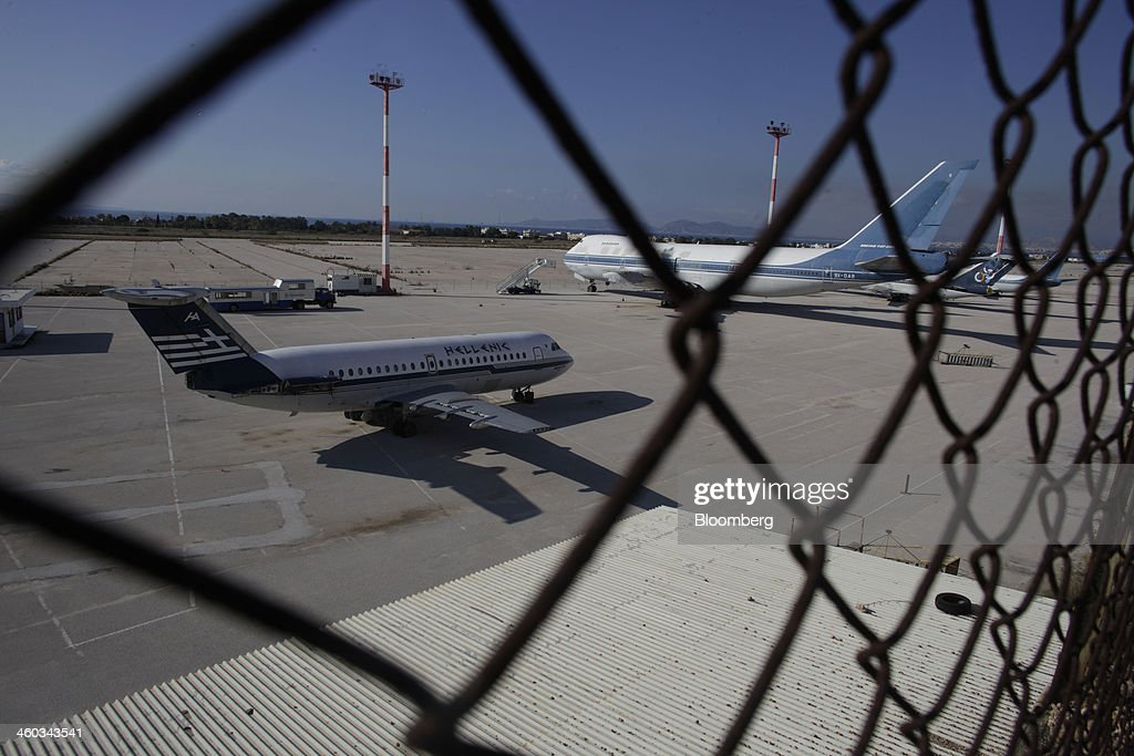 Abandoned passenger aircraft stand on the tarmac at the former Athens International Airport in the Hellenikon district of Athens, Greece, on Friday, Dec. 3, 2014. Hellenikon is the largest of Greece's land development projects, three times the size of the Principality of Monaco. Photographer: Kostas Tsironis/Bloomberg via Getty Images