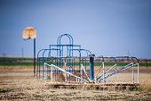 Horizontal image of abandoned playground. Basketball goal, Monkey bars and Merry-Go-Round against blue sky.