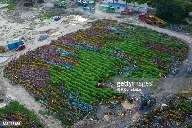 Abandoned share bicycles are seen at a temporary parking lot in Shanghai on August 24 2017 The bikesharing industry has proven wildly popular with...