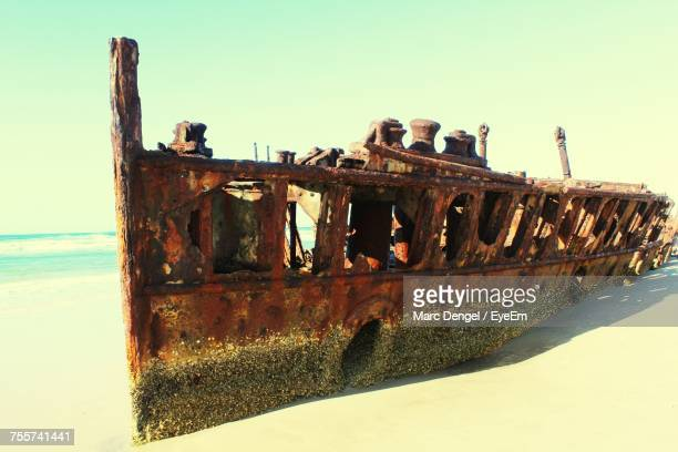 Abandoned Ship At Beach Against Clear Sky During Sunny Day