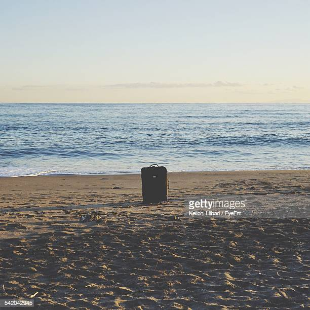 Abandoned Suitcase At Sandy Beach