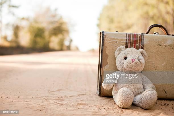 A l'abandon valise avec ours en peluche sur le chemin de terre