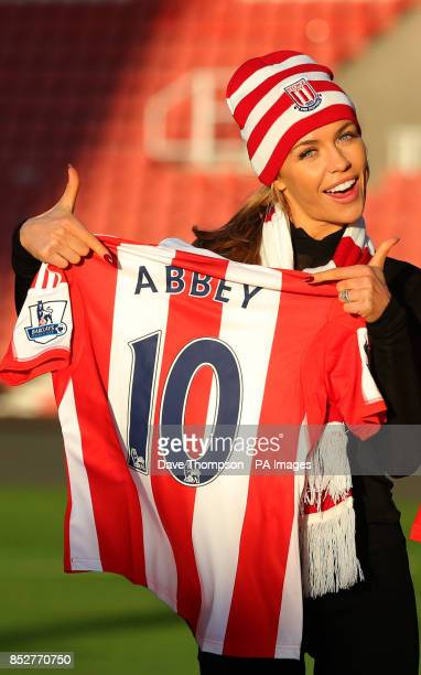 Abbey Clancy holds a Stoke City shirt with her name on it before practicing with her dance partner Aljaz Skorjanec on the pitch at Stoke City's...