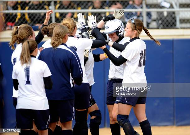 Abby Bergakker of Messiah College is greeted after her solo home run against Coe College during the Division III Women's Softball Championship held...