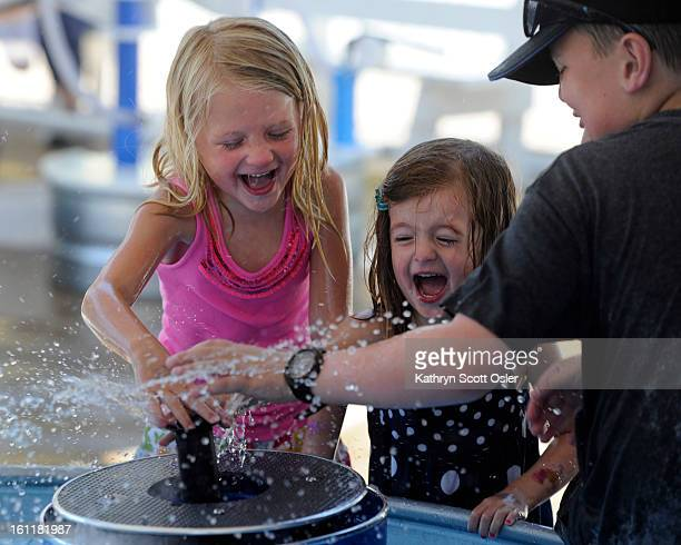 Abby Denler left and sister Greta of Denver plug up one spigot with Liam Kelly right and get a face full of water in return The Children's Museum of...