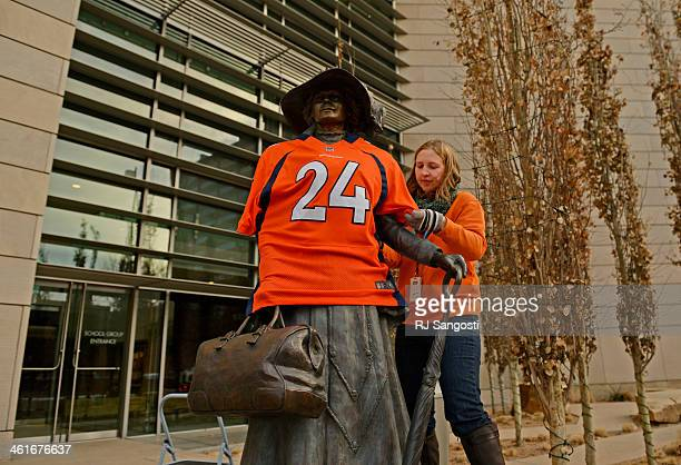 Abby Krause of the History Colorado Center puts a Champ Bailey jersey on a bronze sculpture outside the museum in Denver January 10 2014 The Denver...