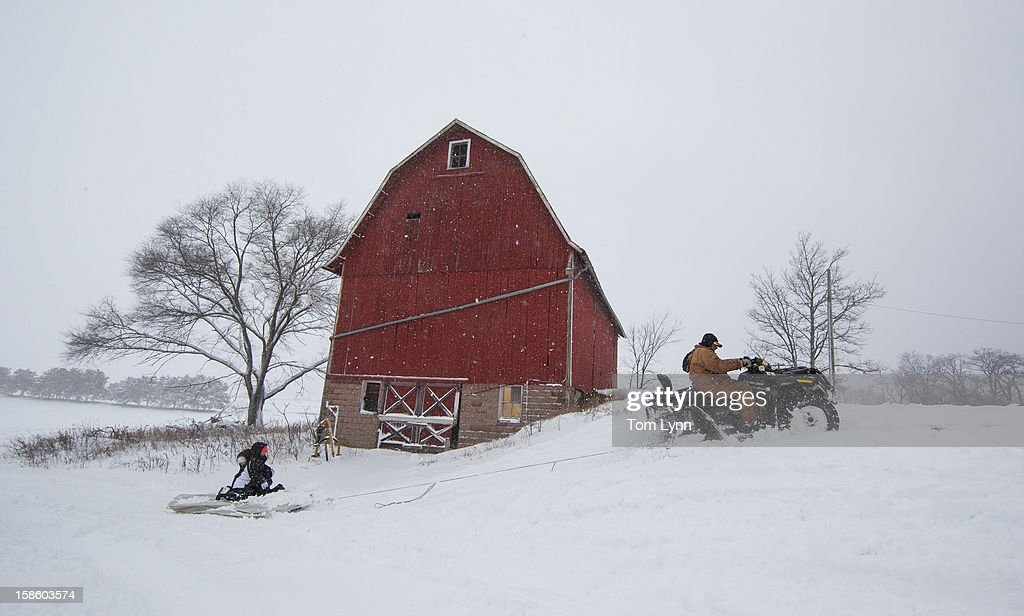 Abby Moon and Carley Moon are pulled on a mattress by their grandfather Clyde Moon's four wheeler during a winter storm in Fairfield, WI December 20, 2012. The State Patrol was warning motorists to stay home as a paralyzing winter storm bore down on Wisconsin In the first significant snowstorm to hit southern Wisconsin in two winters.