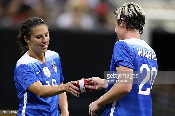 Abby Wambach hands the Captain's armband to Carli Lloyd of the United States as she leaves the field for the final time in her career during the...