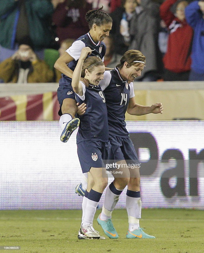 <a gi-track='captionPersonalityLinkClicked' href=/galleries/search?phrase=Abby+Wambach&family=editorial&specificpeople=162757 ng-click='$event.stopPropagation()'>Abby Wambach</a> #14 of the United States celebrates with <a gi-track='captionPersonalityLinkClicked' href=/galleries/search?phrase=Heather+O%27Reilly&family=editorial&specificpeople=736752 ng-click='$event.stopPropagation()'>Heather O'Reilly</a> #9 and <a gi-track='captionPersonalityLinkClicked' href=/galleries/search?phrase=Shannon+Boxx&family=editorial&specificpeople=678532 ng-click='$event.stopPropagation()'>Shannon Boxx</a> (7) in the second half at BBVA Compass Stadium on December 12, 2012 in Houston, Texas. USA won 4-0.