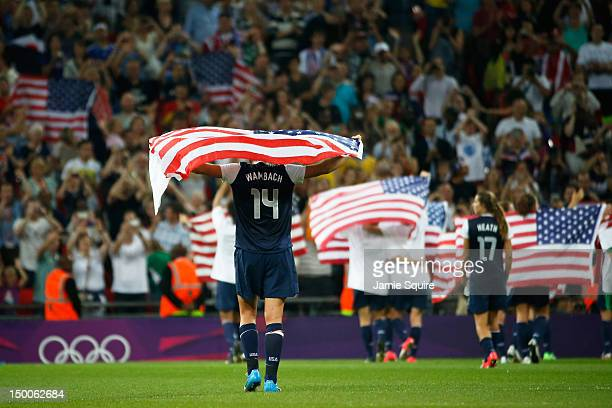 Abby Wambach of the United States celebrates with the flag after defeating Japan by a score of 21 to win the Women's Football gold medal match on Day...