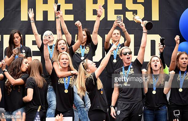 Abby Wambach of the United States of America holds the trophy as she celebrates victory of the 2015 Women's World Cup with teammates during a rally...