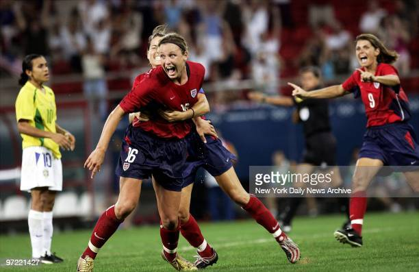 Abby Wambach of the US is hugged by a teammate after scoring the gamewinning goal in overtime against Brazil in the women's soccer gold medal match...